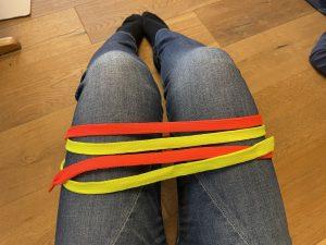 Nimm dir zwei verschiedenfarbige Schürsenkel, binde sie an dem einem Ende zusammen und wickle Sie um deine Oberschenkel!